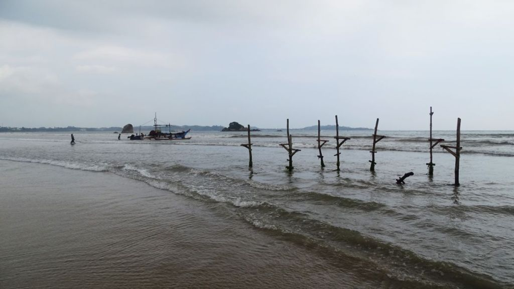 Wooden poles stuck in shallow sea used by stilt fishermen and fishermen getting on their wooden boat in Weligama