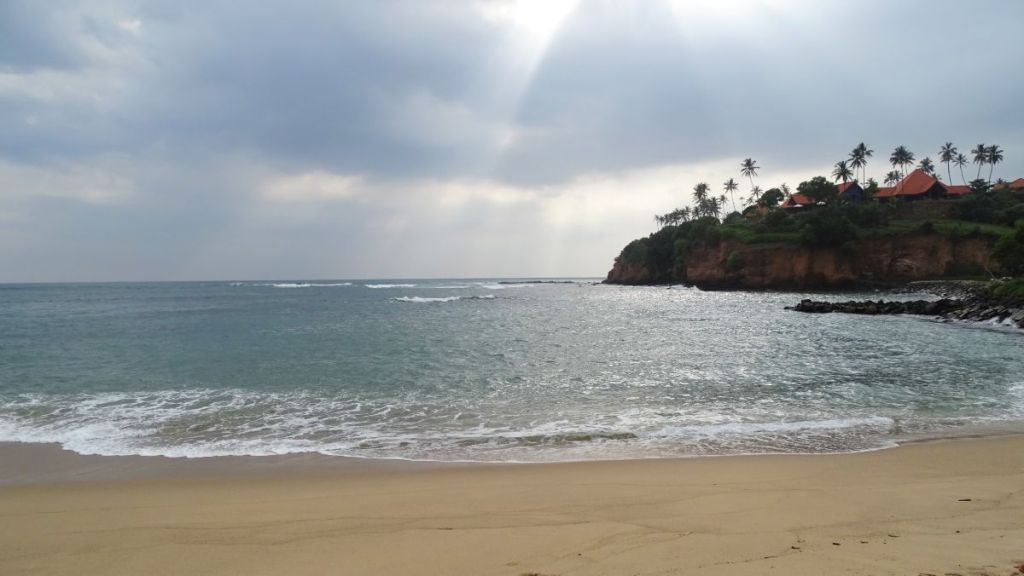 Sun rays lit the sea in Jungle Beach Bay in Walliwala the red cliffs with a holiday resort visible in one end of the bay