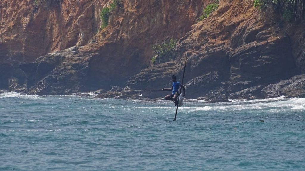 A young Sri Lankan man sitting on a stilt immersed in the sea, angling. A red rock cliff rising behind him.