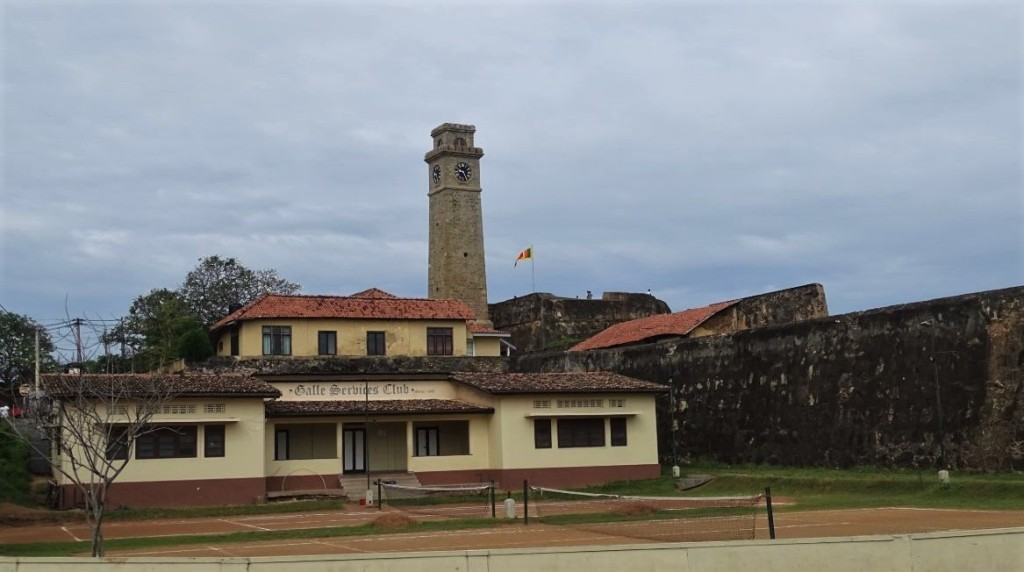 A view at the clocktower and ramparts of Galle with the Sri Lankan flag at one of the  bastions