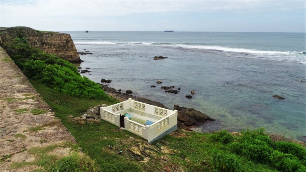 A small, white, walled Muslim tomb set on a cliff just outside the walls of Galle Fort, above the sea