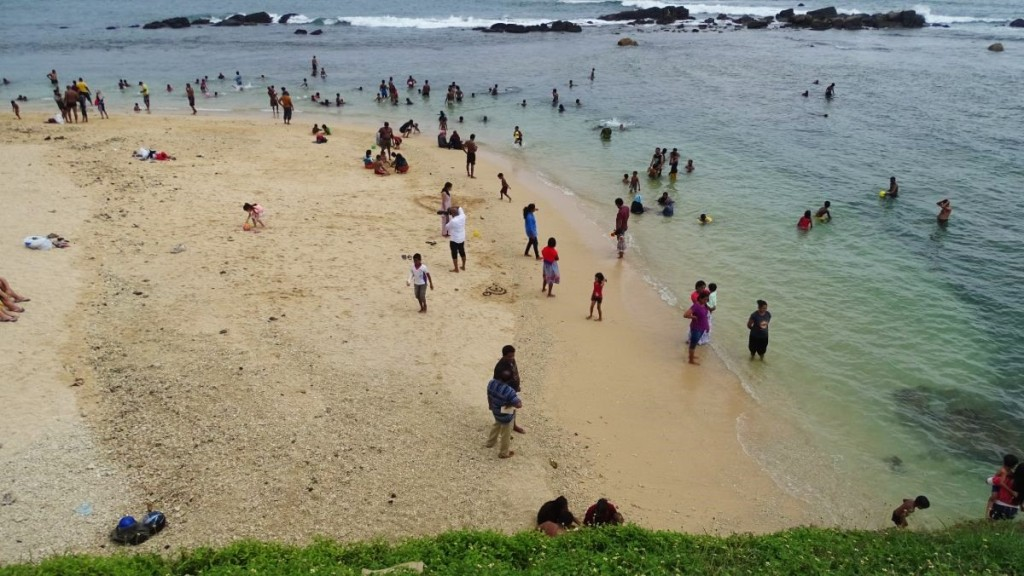 A small sandy beach with full-dressed Sri Lankans bathing and strolling