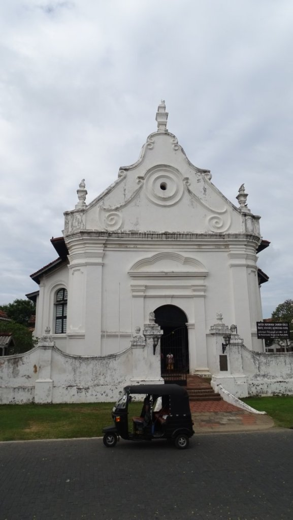 A tuk tuk standing in front of baroque, white-washed Dutch Reformed Church in Galle