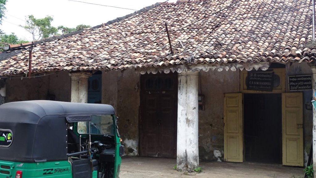 A tuk tuk stands in front of a dilapidated one storied building with a colonnade and a red-tiled roof in Matara