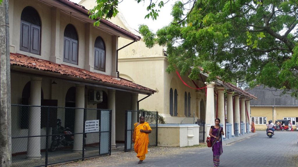 A lady in a Sari and a yellow-robed monk walk pass a sand-stone coloured Dutch church with a colonnade verandah.