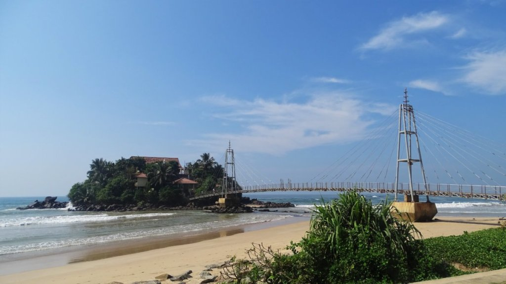 A pendestrian bridge joins a sandy beach with a tiny Pigeon Island where a Buddhist temple hides among greenery