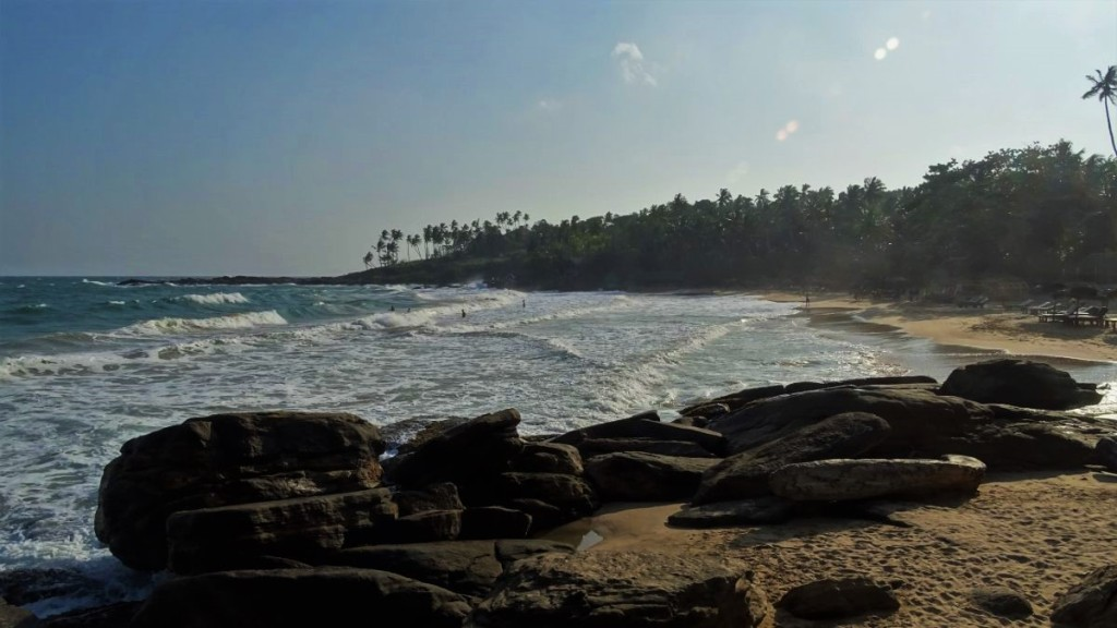 High waves at a cove of Goyambokka beach, surrounded with thick coconut grove