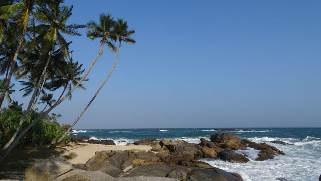 A rocky outcrop and a rough sea around it at Goyambokka beach in Tangalla