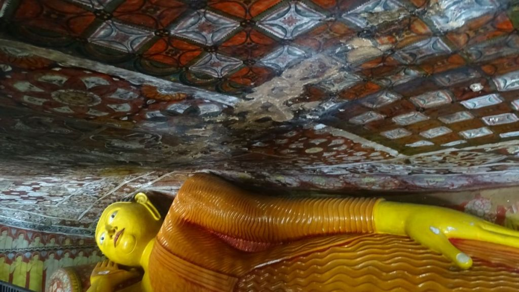 A yellow, reclining Buddha statue located under a painted, very low ceiling of the natural cave in Mulkirigala cave temple