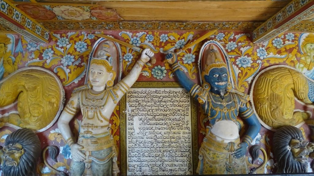 Statues of a blue bearded warrior and a white warrior hold swords above a plaque with Sinhala script in a cave temple in Mulkirigala