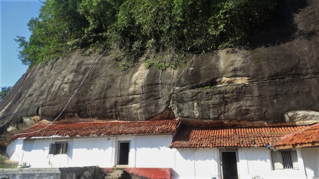 A simple, white-walled entrance to the temples hidden in natural caves in Mulkirigala, Sri Lanka