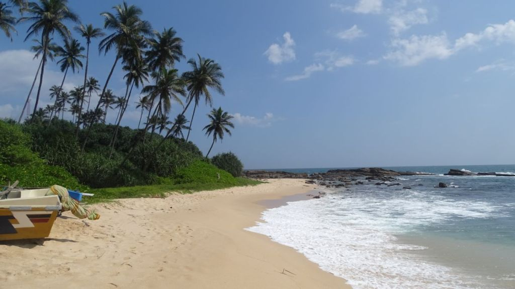 A narrow strip of sand, a rocky peninsula and greenery beyond on the Silent Beach in Tangalla