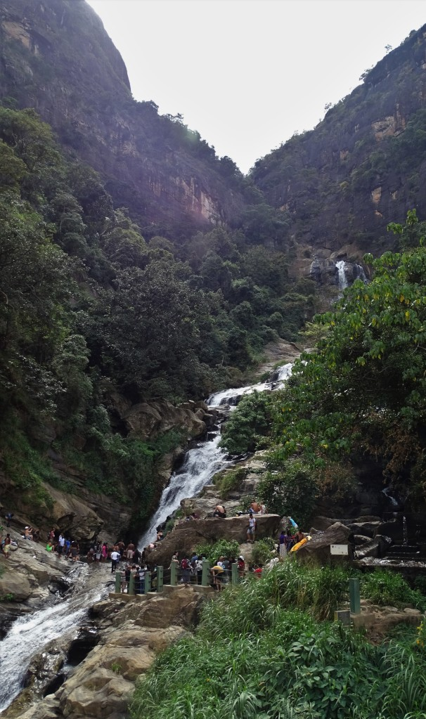 25 meters Ravana Falls cascading down the rocks and a crowd of tourists standing right across one of its cascades.
