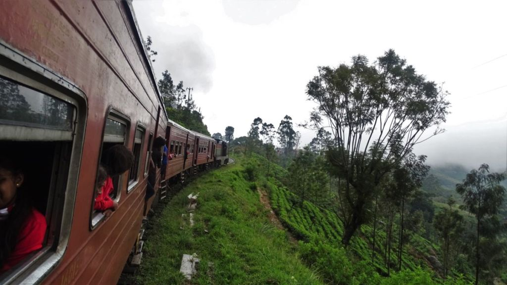 School children in uniforms look through the windows of a train passing through tea gardens between Ella and Haputale