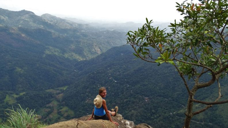 Author sitting at the rocky outcrop with expansive views over a green valley near Ella Rock in Sri Lanka