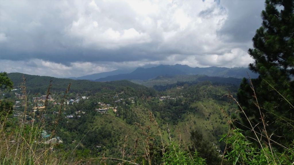 Expansive views at rugged peaks in the background and green hills over which Ella town spreads