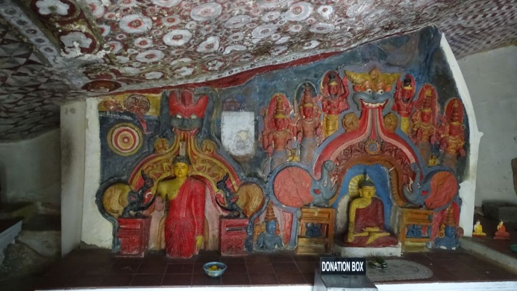 A cave with sculpures of Buddha and painted ceiling