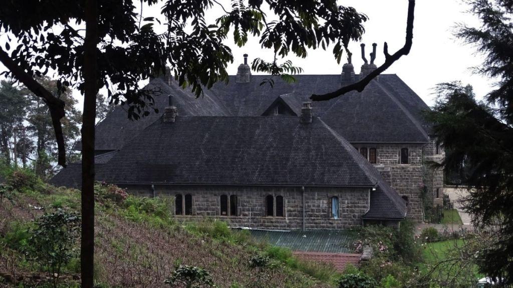 A grey, stone formidable European building housing Adisham Monastery in Haputale