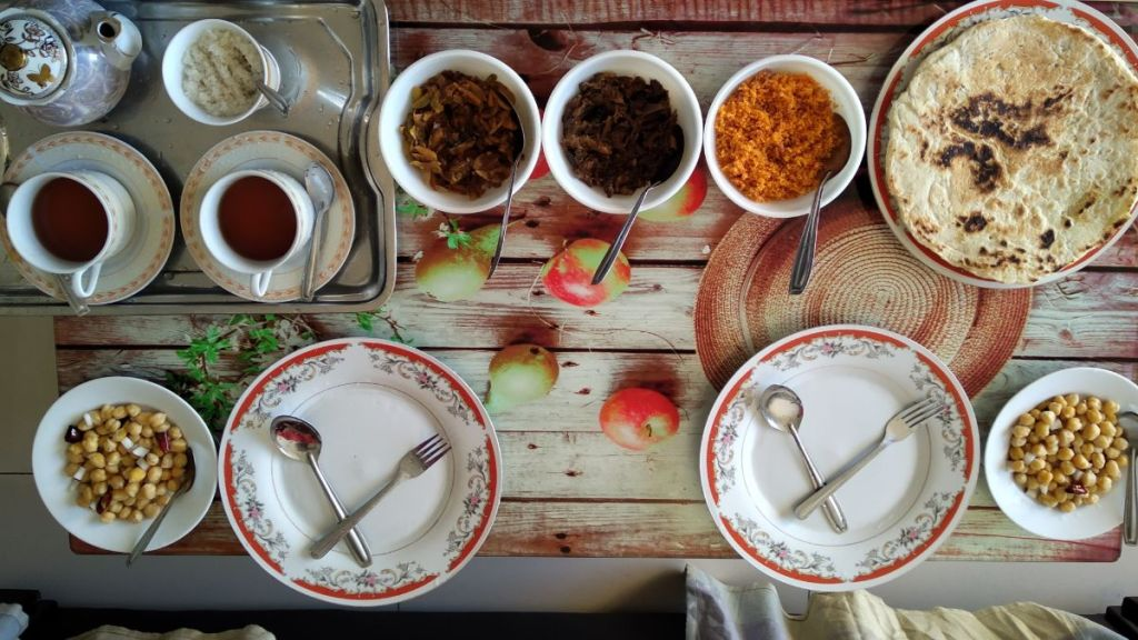 Elegantly presented traditional Sri Lankan breakfast consisiting of coconut flatbreads, chickpea with chilli, smabar, dried firsh and local black tea.