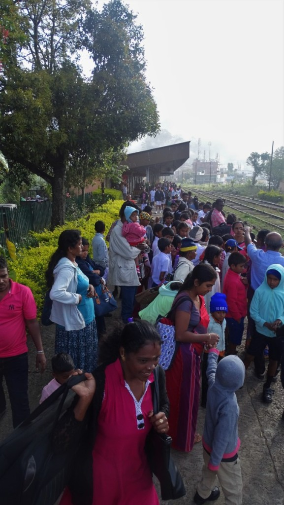 A crowd of locals, mostly children, waits a the train platform in Haputale