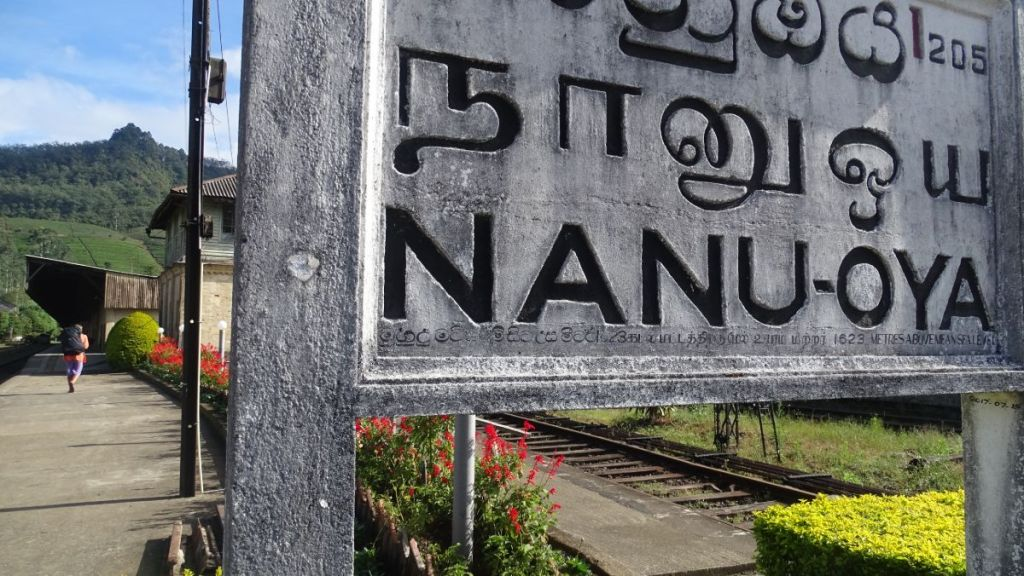 A concrete board with Nanu Oya name written in English, Tamil and Sinhala scripts and the train platform behind it