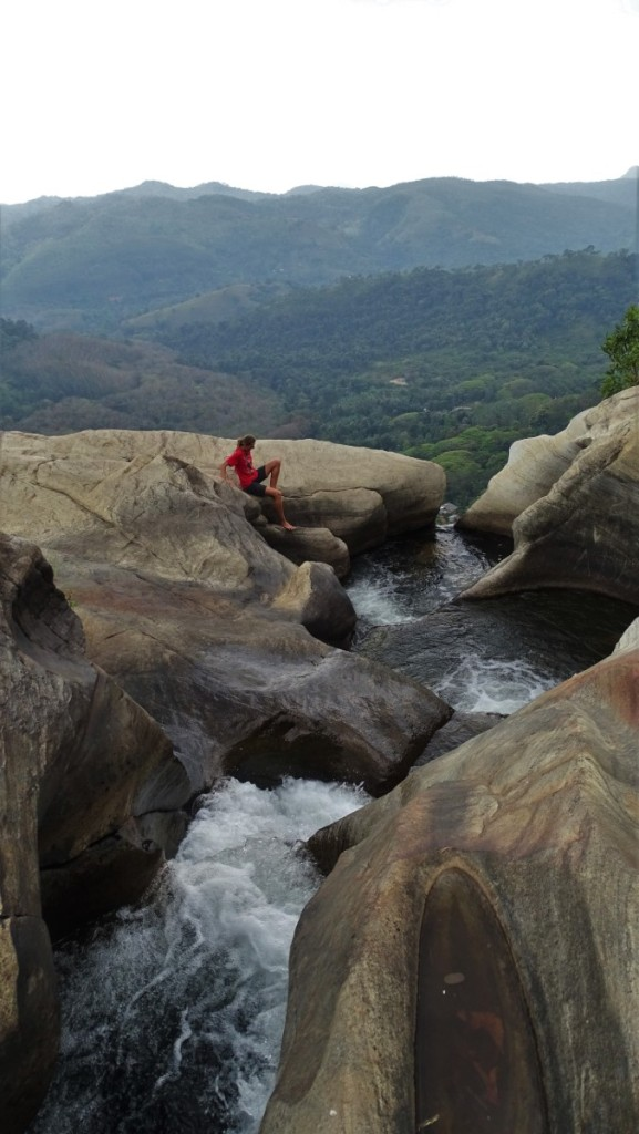 Author sliding down the rock to enter a small, thigh deep pool at the directly above Diyaluma fall