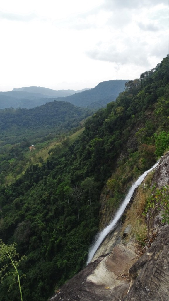 A shot from above at the Diyaluama Fall tumbling down and the green mountains behind