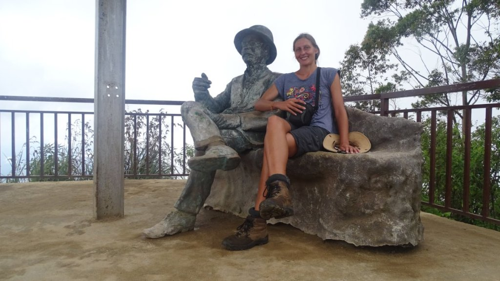 Smiling author sits on a stone bench next to Mr Lipton's statue at Lipton's Seat in Sri Lanka