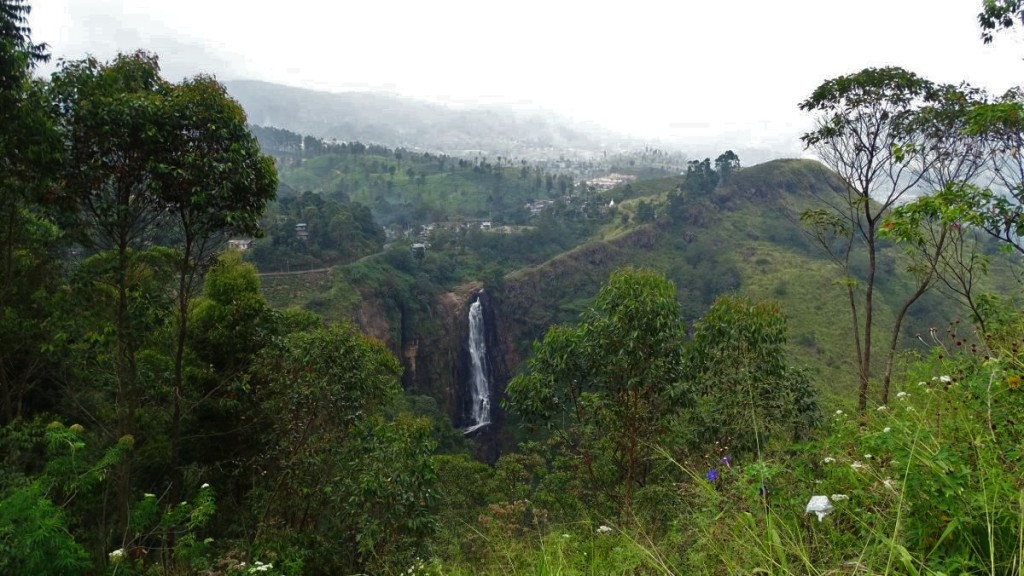 Tall, powerful Devon waterfall falling off a sharp ridge among greenery