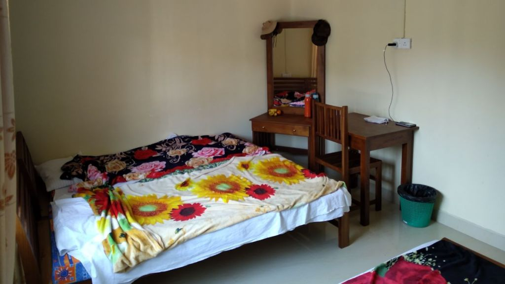 A picture of a room at a guest house in Nanu Oya, with a double bed covered with a blanket, a desk, a chair and a dressing table