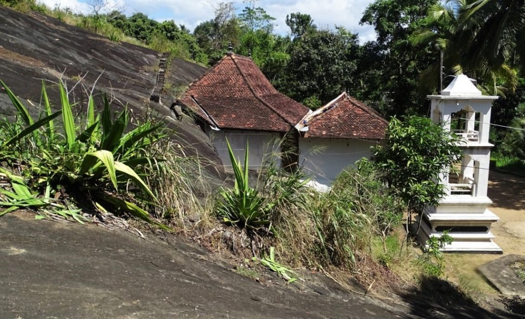 A small whitewashed, tile-roofed temple blending into the natural rock in Degaldoruwa near Kandy