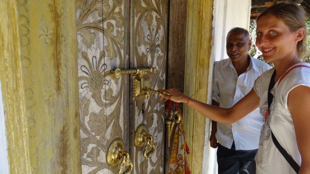 The author using gigantic keys to open a golden lock in the painted doors of Galmaduwa temple