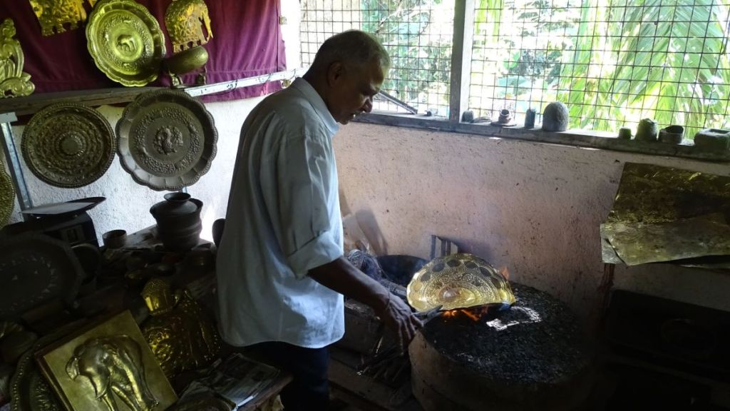 An artisan working with the decorative brass plates over open fire in his workshop in Sri Lanka
