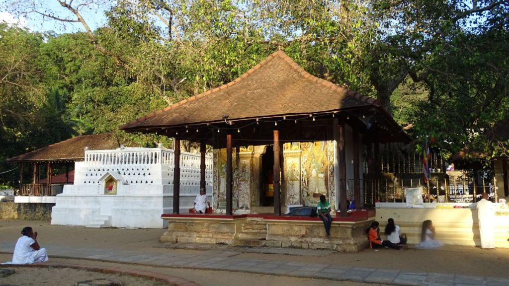 People sit athe portico of a small square shrine with frescoes on outer walls, at Natha Devale in Kandy