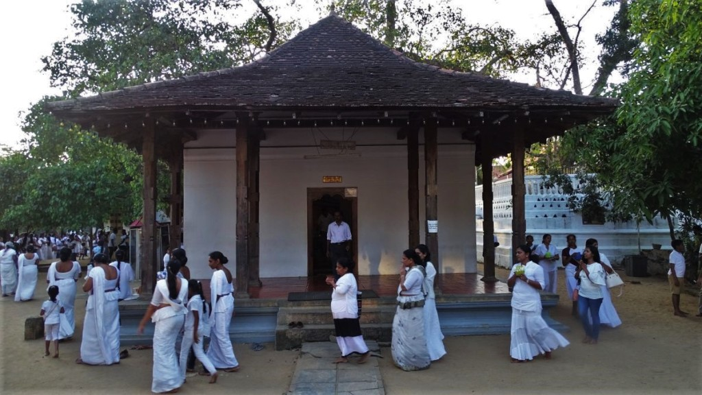 Women in white dresses walk around one of the temples near Natha Devale in Kandy