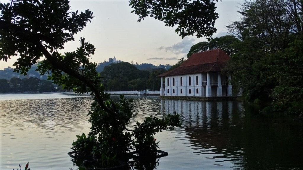 A white two storied building with a tiled roof of Royal Bath stands on a peninsula at Kandy Lake
