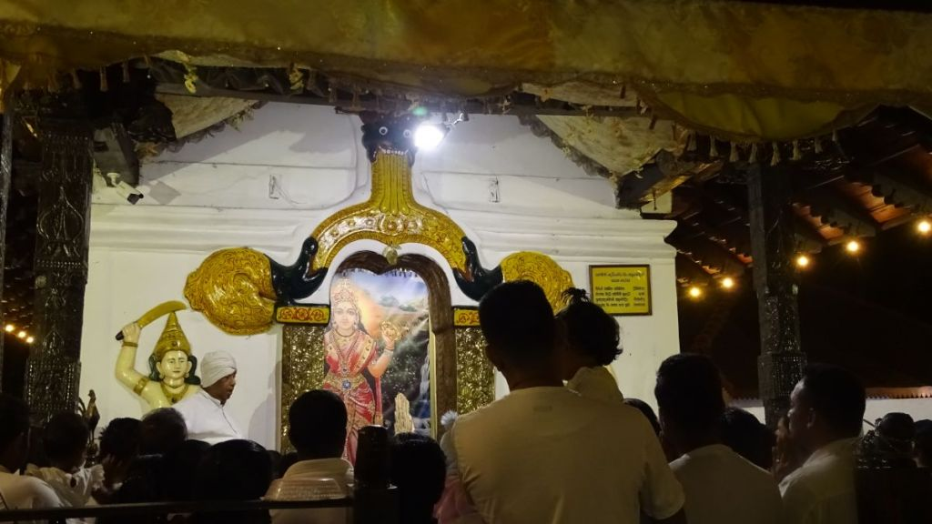 A small crowd gathers in front of Pattini Devale in Kandy for the evening prayer