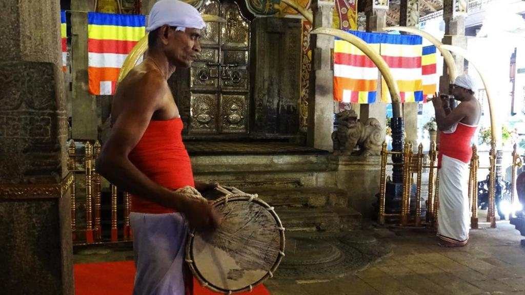 A drummer and a trumpeteer dressed in white dhotis, white headwear and play in front of the doors adorned with ivory at the Temple of the Sacred Tooth Relic in Kandy