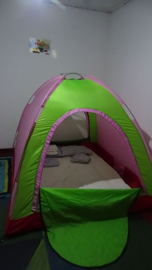 A small tent with bedding inside set up inside a room for Couch Surfers