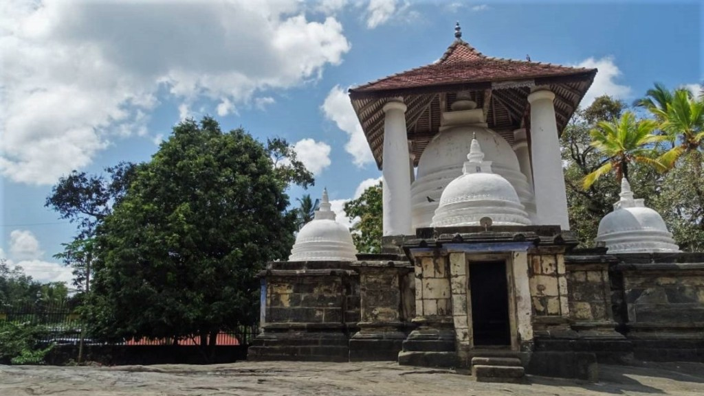 Gadaladeniya temple made of stone with a white stupa under a sloped, tiled roof
