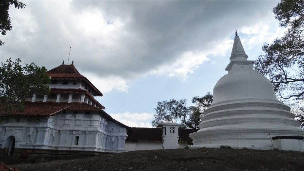 A two storied white washed building of Lankathilake temple covered with tiled roof and a white stupa standing on bare rock near Kandy, Sri Lanka