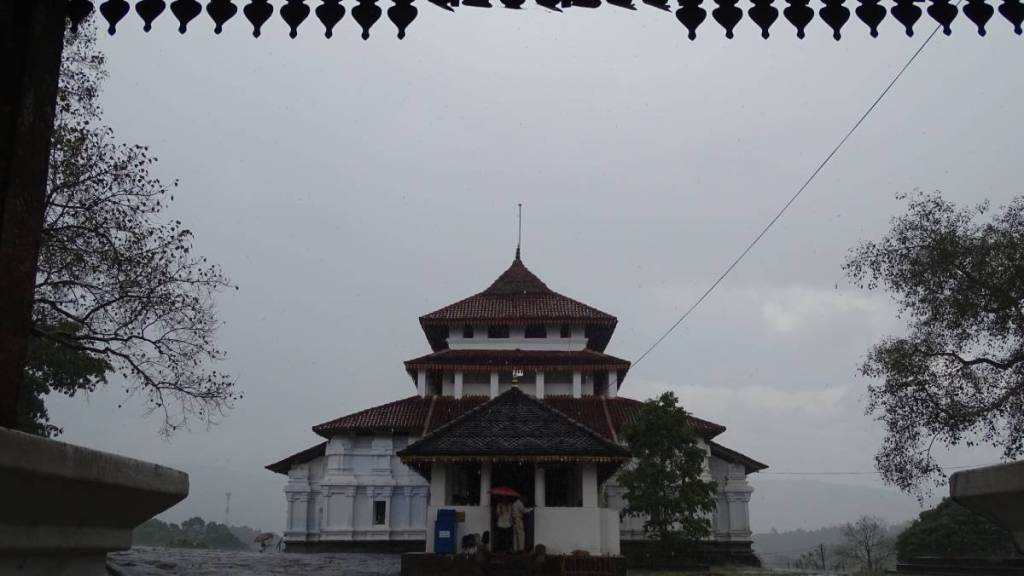 A two storied white building of Lankathilake templein the downpour