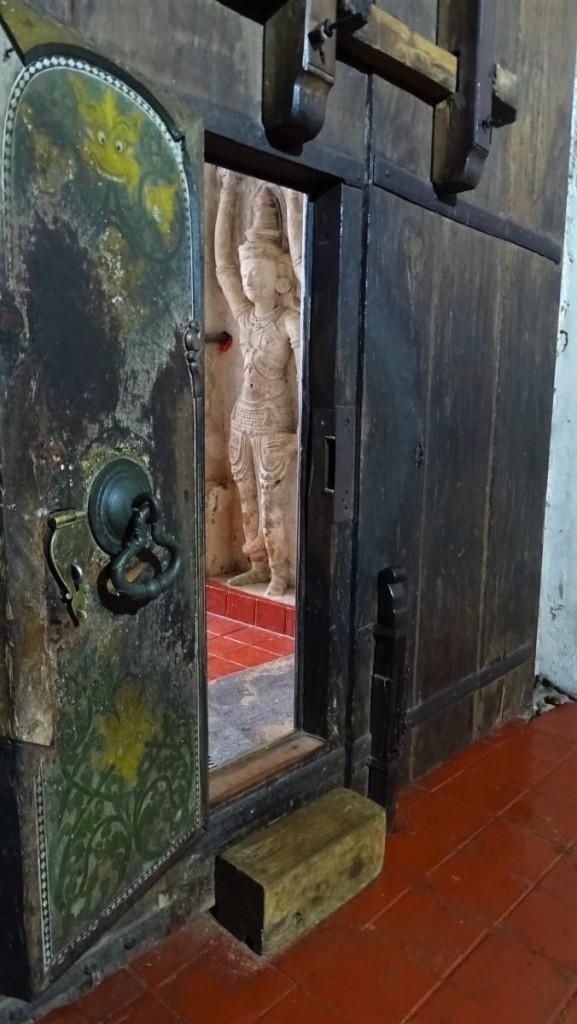 Old, wooden painted door of Lankathilake temple show a sculpture in a vestibule