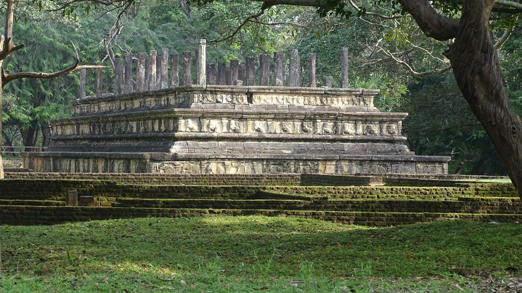 A pyramidal stone platform with the remnants of columns on top set amongh the greenery at Polonnaruwa sacred city