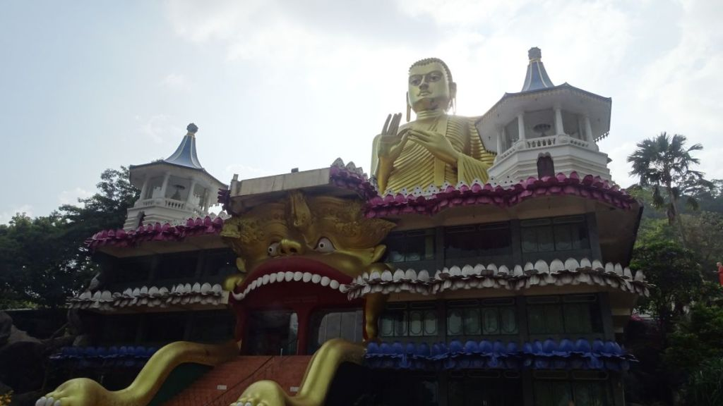 A new, tacky building of golden temple in Dambulla, featuring a giang golden Buddha and a entrance in the form of a mouth of a lion