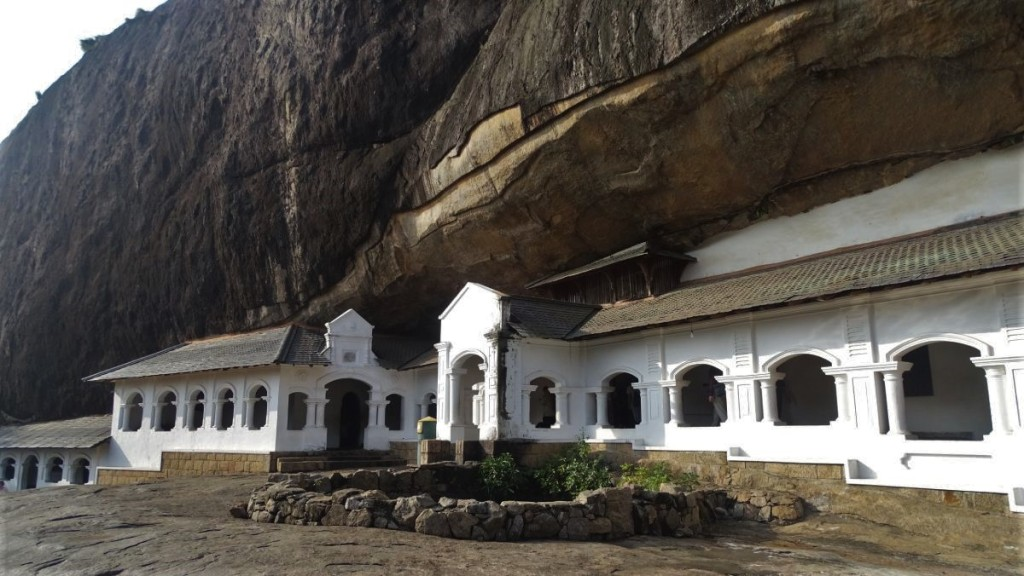 A white arcade entrance to the Dambulla Cave Temple blended with an overhanging rock