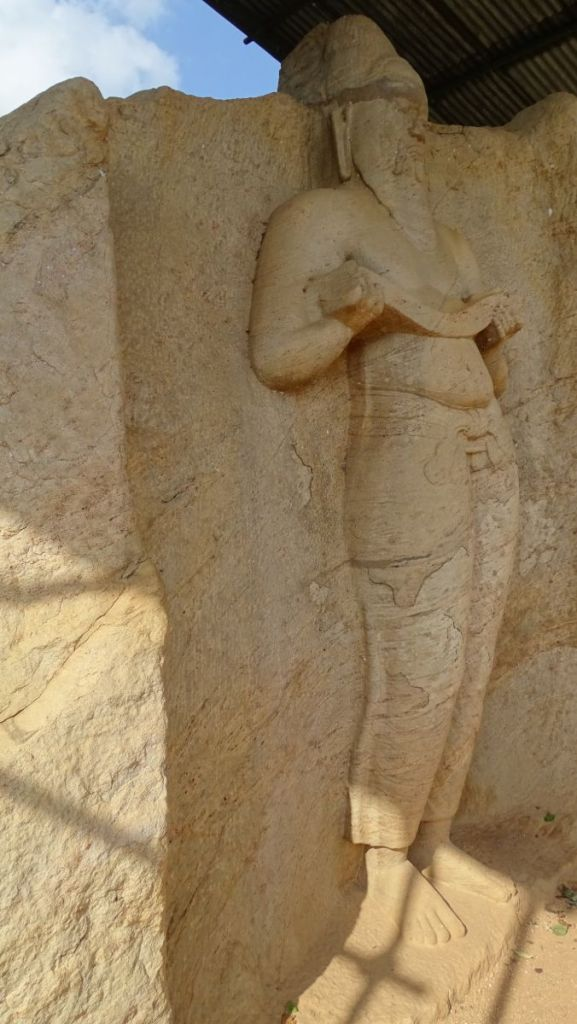 A stone, standing statue of a sage or a king standing near the reservoir in Polonnaruwa