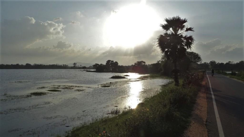 A cyclist on an empty, smooth road along the Parakrama Samudraya reservoir in Polonnaruwa