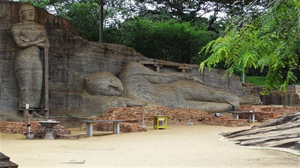 A cross-armed standing statue and a reclining Buddha statue cut straight out of a granite rock at Gal Vihara in Polonnaruwa