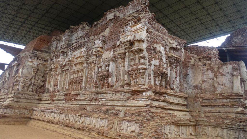 Modern roof protects roofless ruins of a brick Tivanka Image house at Polonnaruwa ancient city
